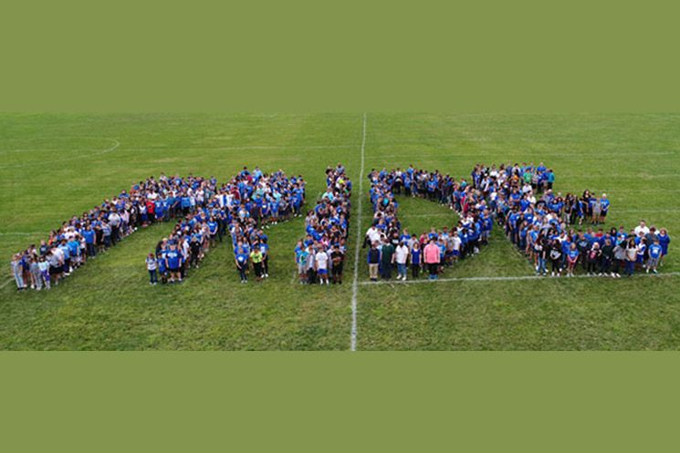 Students from Springbrook elementary create the word PRIDE while standing on the football field.