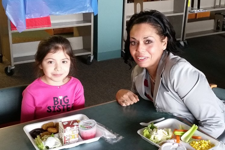 Teacher eats lunch with student.